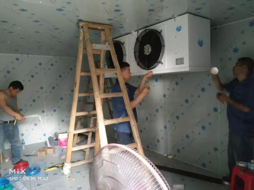图为安装工人正在安装冷风机