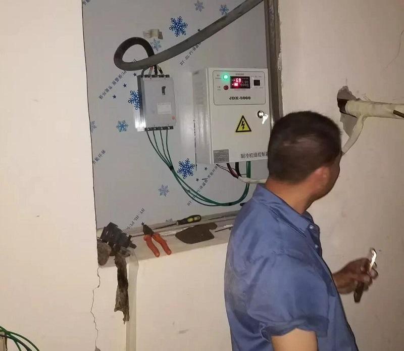 图为安装师傅正在调试组机控制箱