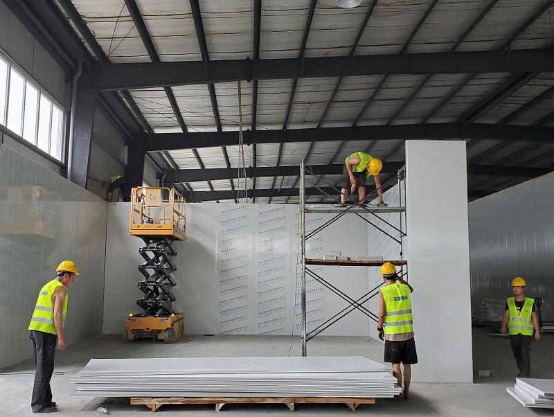 图为工人们正在安装聚氨酯双面彩钢板保温库板