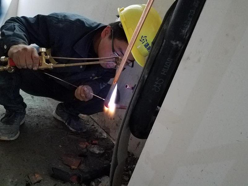 图为工作人员正在焊接铜管