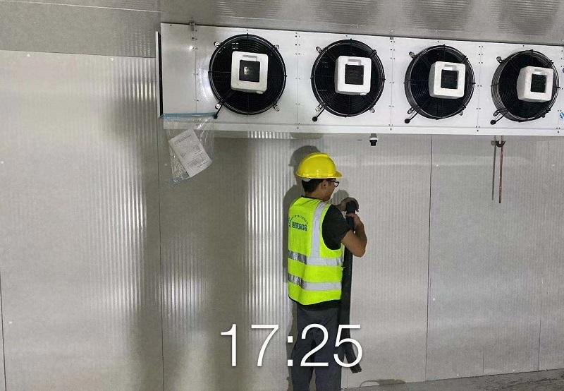 图为工人正在对冷风机管道加保温棉