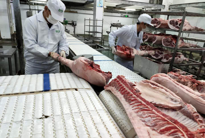 图为工作人员正在处理猪肉