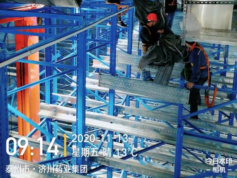 图为工人们正在安装货架和布袋风管